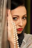 Girl in retro style. red lips. Girl near a wall with beads in her hands Royalty Free Stock Image