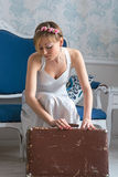 Girl in retro style wedding dress collects a vintage suitcase in Royalty Free Stock Images