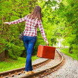 Girl with retro suitcase walking on the railway Stock Images