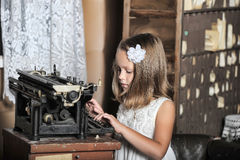 Girl with a retro typewriter Royalty Free Stock Photos