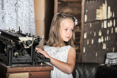 Girl with a retro typewriter Stock Images