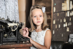 Girl with a retro typewriter Stock Image