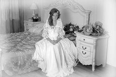 Girl in a retro white dress is sitting Royalty Free Stock Images