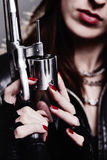 Girl with a revolver. Rebel girl with motorcycle gloves holding a revolver Stock Images