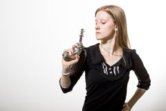 A girl with revolver. A blonde girl holds the revolver. She has imperious look Stock Image