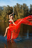 Girl revolves around  pole dancing in a red dress. Royalty Free Stock Photos