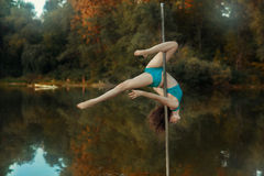 Girl revolves on the pole for dancing performing tricks. Stock Image