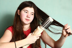 Girl revolving brush to straighten hair. Teen pretty girl with long thick dark hair use revolving straightener brush to straighten hair Royalty Free Stock Photos