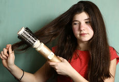 Girl revolving brush to straighten hair. Teen pretty girl with long thick dark hair use revolving straightener brush to straighten hair Stock Photography