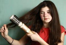 Girl revolving brush to straighten hair Stock Photography