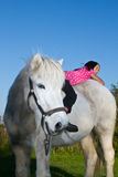 Girl ridding a white horse in denmark Royalty Free Stock Image