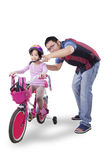 Girl ride bicycle with her father Royalty Free Stock Photos