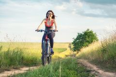 Girl ride on a bike on the field at the summer time. Stock Photography