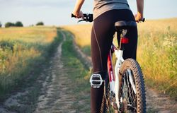 Girl ride on a bike on the field at the summer time. Royalty Free Stock Photos