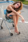 Girl ride shopping cart on pavement stock images
