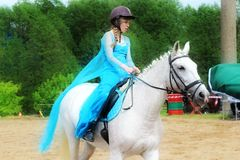 Girl rider in a blue dress. Royalty Free Stock Images