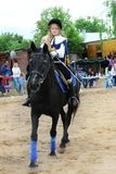 Girl rider in the form of binding performs Musketeers competition program. Stock Photos