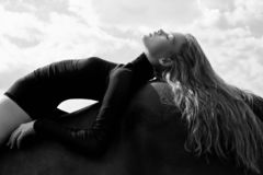 Girl rider lies bent on a horse in the field. Fashion portrait of a woman and the mares are horses in the village in the sky. Blonde woman lies and dreams on a royalty free stock photography