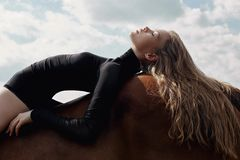 Girl rider lies bent on a horse in the field. Fashion portrait of a woman and the mares are horses in the village in the sky. Blonde woman lies and dreams on a royalty free stock images