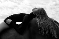 Girl rider lies bent on a horse in the field. Fashion portrait of a woman and the mares are horses in the village in the sky royalty free stock photography