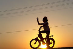 The girl rides bicycle. The little girl rides bicycle on sunset stock photos