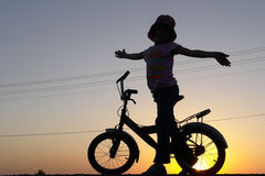 The girl rides bicycle. The little girl rides bicycle on sunset stock image