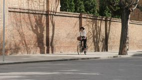 A girl rides a bicycle along the road along the stone wall stock footage