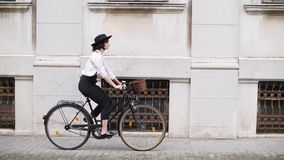 A girl rides a bicycle along the road along the buildings stock footage