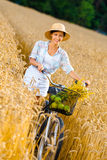 Girl rides bicycle with apples and flowers in rye  Royalty Free Stock Photos