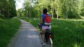 A woman rides on summer Park Bicycle. A girl rides a Bicycle with a backpack, rear view stock footage
