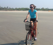 Girl rides a bicycle on the beach Stock Photography