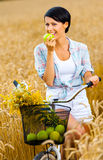 Girl rides bicycle and eats apple in rye field Royalty Free Stock Photo