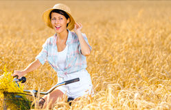 Girl rides bicycle with flowers in rye field Royalty Free Stock Images