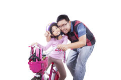 Girl rides bicycle with her dad Stock Photo