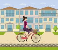 A girl rides a bicycle home in her neighborhood. Woman is cycling from shop with  bag with food Stock Photography