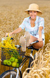 Girl rides bicycle putting legs on it in rye field Royalty Free Stock Photography