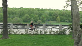 Girl rides a bicycle by river bank. Sporty girl walking on bike in a park. Girl rides a bicycle by river bank. Sexy young woman rides bicycle along embankment on stock footage