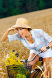Girl rides bicycle in rye field Stock Photo