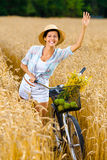 Girl rides bicycle and waves hand in rye field Stock Photos