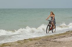 Girl rides a bike on the beach. Royalty Free Stock Image