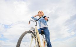Girl rides bike sky background. Woman rent bike to explore city copy space. Bike rental shops primarily serve people who. Do not have access to vehicle royalty free stock images
