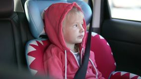 Girl rides in a car in a car seat. A child falls asleep in a car seat in a car stock video