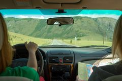 The girl rides in the car in the passenger seat and looks at the paper map looking for the desired route and indicates the road stock photography