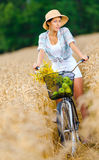 Girl rides cycle with apples and flowers Stock Photography