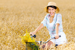 Girl rides cycle in rye field Royalty Free Stock Image