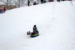 The girl rides down a hill on an inflatable sled. Winter fun. The action takes place on the outskirts of the city of Monino. Residents of the town come with stock image