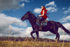 Girl rides on a horse in red dress developing in the field on sky Stock Photography