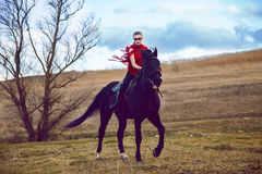 Girl rides on a horse in red dress developing in the field on sky Stock Photos
