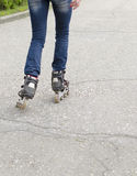 Girl rides on roller skates on asphalt. Legs in rollers Royalty Free Stock Photos