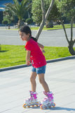 The  girl  rides on roller skates in the park Royalty Free Stock Photo
